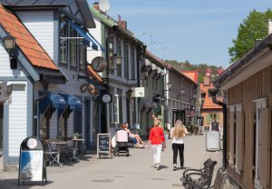 Sigtuna, Sweden - May 23, 2016 : View of the old town street of Sigtuna. People are walking and shopping at the main street of old town on a sunny spring day.